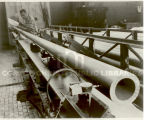 A worker, standing next to a section of pipe