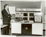 "A man stands next to a promotional display entitled,""GE Progress in Measurement for the..."